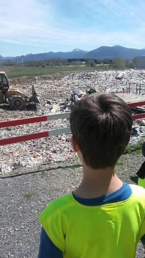 enfant au centre de tri de capvern devant les déchets enfouis